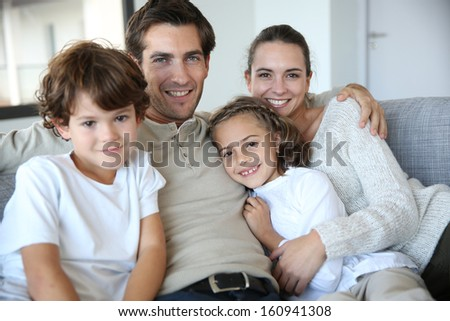 Happy family of four relaxing in sofa