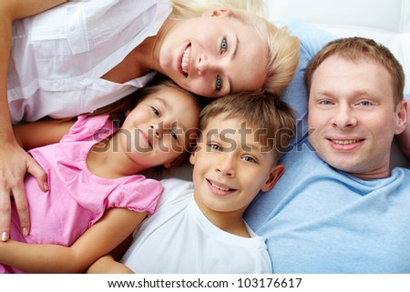 Happy family of four resting at home