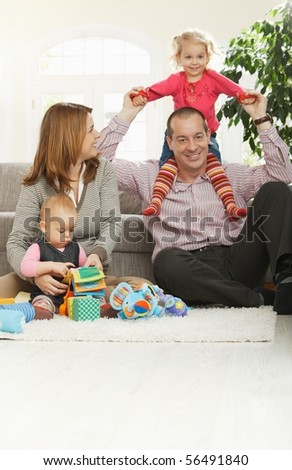 Happy family of four sitting at home on floor of living room, smiling girl sitting in daddy's neck.