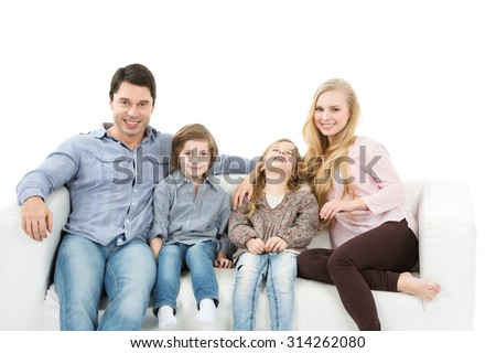 Happy family of four sitting on a sofa. Isolated on white background. - stock photo