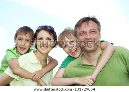 happy family of four spends time outdoors in the summer - stock photo