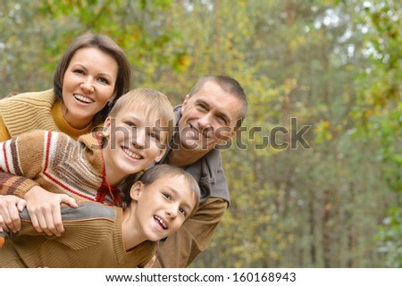 Happy family of four standing together in the park in autumn
