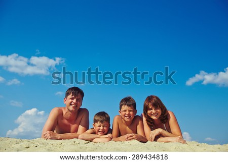 Happy family of four sunbathing on hot summer day