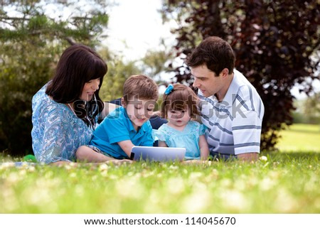 Happy family of four using a digital tablet outdoors - stock photo