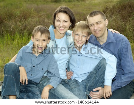 happy family of four walking in park in summer