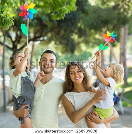 Happy family of four walking with children on vacation day at park  - stock photo