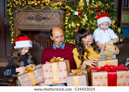 happy family of four with gift box over living room and christmas tree background
