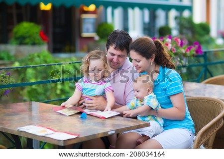 Happy family of four, young parents and their two kids, adorable toddler girl and cute baby boy enjoying lunch at a beautiful outside cafe in a small traditional German town  - stock photo
