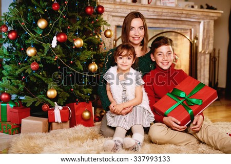 Happy family of mother and two kids looking at camera on Christmas evening at home