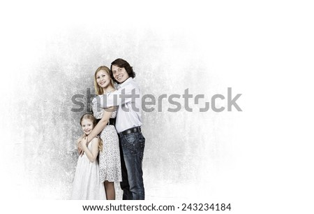 Happy family of mother father and daughter against cement wall - stock photo