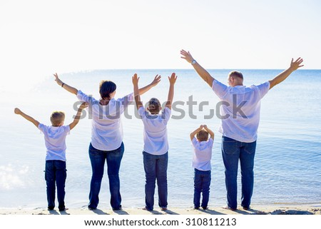 happy family of mother, father and three sons cheering on beach. Family enjoying the sunrise sunlight on seaside during summer vacations, family on vacations concept