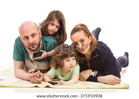 Happy family of mother,father and two kids laying on floor  - stock photo