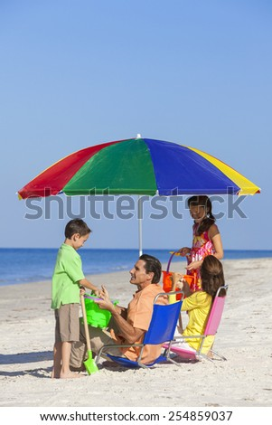 Happy family of mother & father, parents daughter & son children having fun in deckchairs under an umbrella on a sunny beach