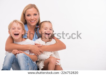 Happy family of mother  son and daughter smiling  embracing  looking  at camera  isolated on white background with copy place - stock photo