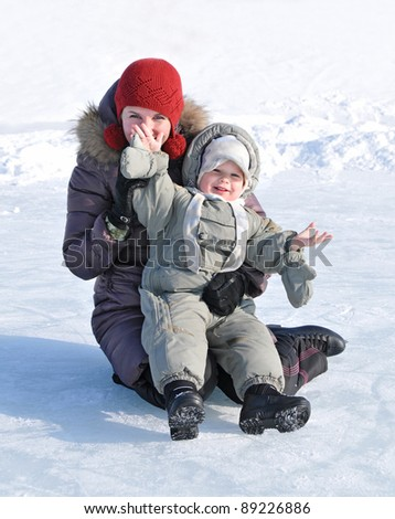 happy family of mother with baby playing in the snow winter park - stock photo
