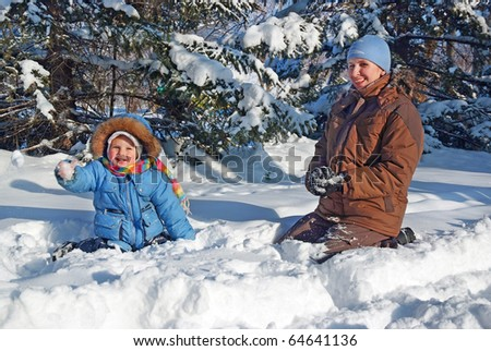 happy family of mother with kid playing in the snow winter park - stock photo