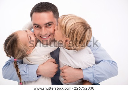 Happy family of son and daughter  kissing father smiling  embracing  looking  at camera  isolated on white background with copy place - stock photo