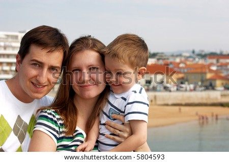 Happy family of three at European destination. Typical Mediterranean small town with orange roofs visible on background