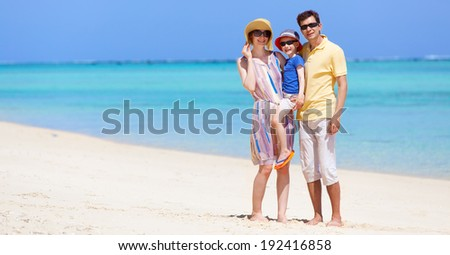 happy family of three at the beach - stock photo