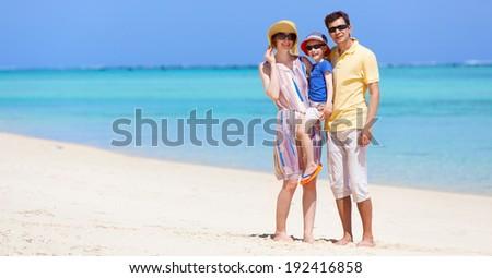 happy family of three at the beach - stock photo