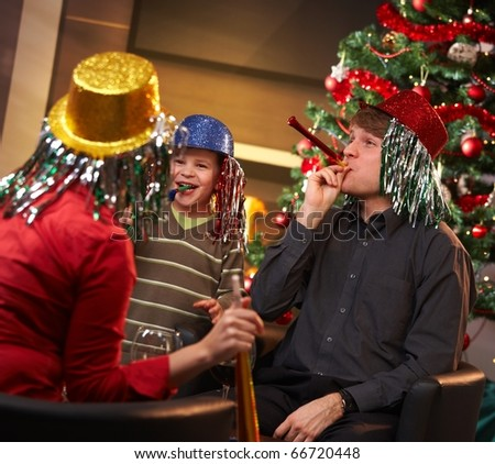 Happy family of three celebrating in new year eve hat at home.? - stock photo