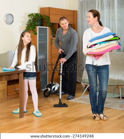 Happy family of three cleaning at home all together. Focus on girl