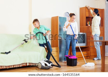 Happy family of three cleaning with vacuum cleaner in living room