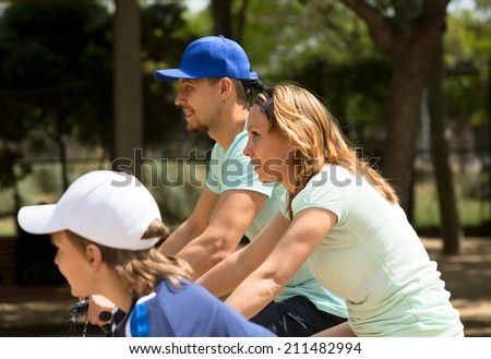 Happy family of three cycling on city street in summer day - stock photo
