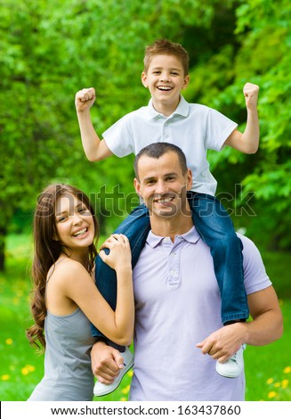Happy family of three. Dad keeps son on shoulders. Concept of happy family relations and carefree leisure time - stock photo