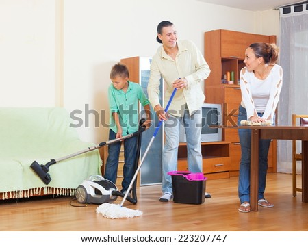 Happy family of three doing house cleaning with vacuum cleaner