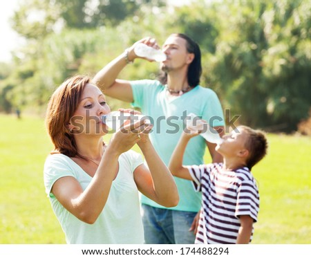 Happy family of three drinking from plastic bottles in summer park - stock photo