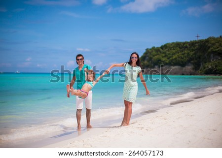 Happy family of three enjoying beach vacation
