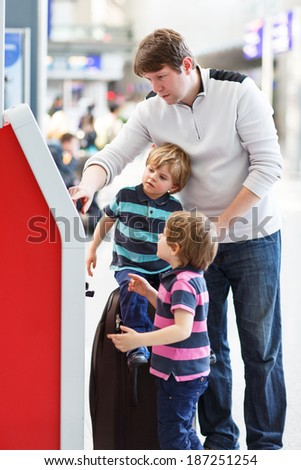 Happy family of three: Father and two little sibling boys at the airport, traveling together and checking in at terminal. - stock photo