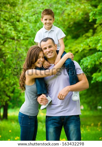 Happy family of three. Father keeps son on shoulders. Concept of happy family relations and carefree leisure time - stock photo