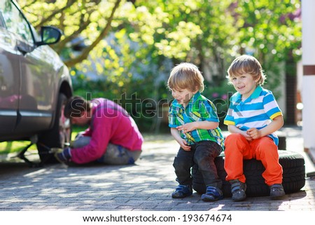 Happy family of three: father repairing car and changing wheel, two little sibling boys sitting on big wheel, outdoors - stock photo
