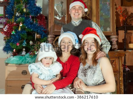 Happy family of three generations in santa hats celebrating Christmas in home
