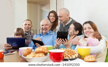 Happy family of three generations or group of friends with electronic devices over tea at home