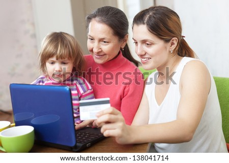 Happy family of three generations with laptop, paying by credit card in internet store - stock photo
