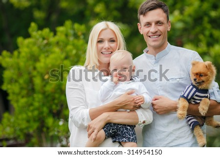 happy family of three having fun and smiling outdoor. Happy young family spending time together outside. Happy mother, father and son