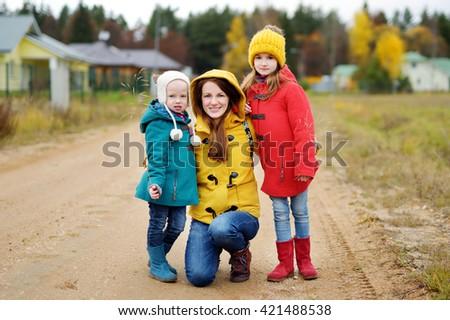 Happy family of three having fun on beautiful autumn day outdoors - stock photo