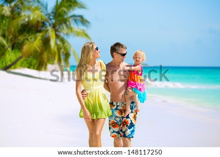 Happy family of three having tropical vacation - stock photo