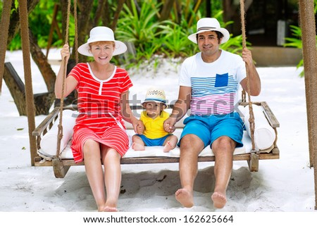 Happy family of three having tropical vacation. Mother, father and baby swinging on the beach .  - stock photo