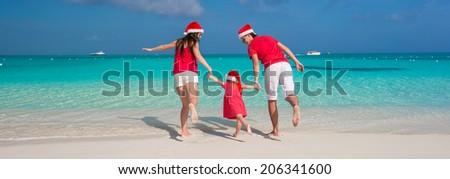 Happy family of three in Christmas Hats having fun on white beach - stock photo