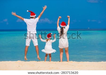 Happy family of three in Santa Hats on beach - stock photo