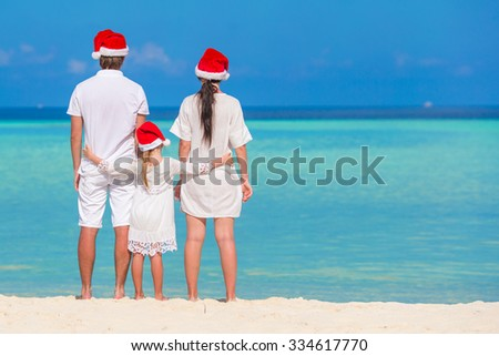 Happy family of three in Santa Hats on beach during Christmas vacation - stock photo