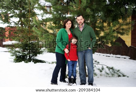 Happy family of three in the red green sweaters outdoor near the house  at the snow winter day