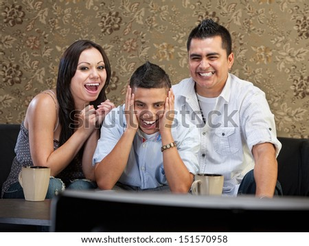 Happy family of three laughing at a television - stock photo