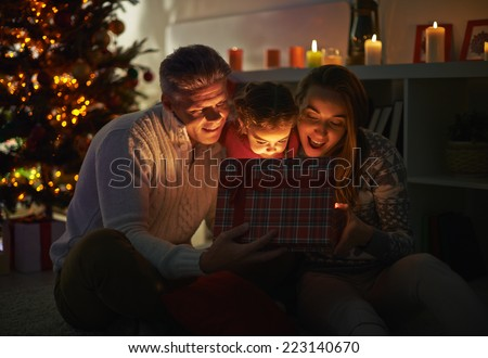 Happy family of three looking into open giftbox on Christmas night - stock photo