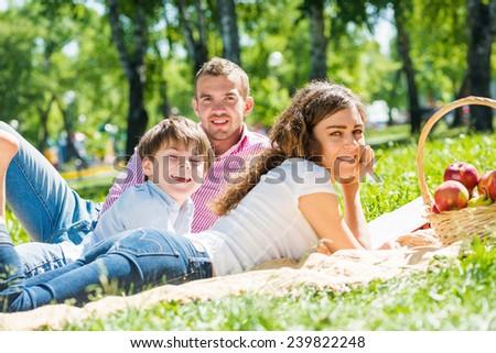 Happy family of three lying in summer park - stock photo