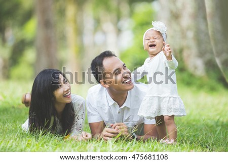 Happy family of three lying in the grass in autumn